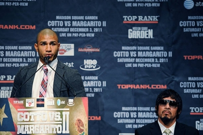 Professional boxer Miguel Cotto speaking at the podium during a press conference about his upcoming fight with Antonio Margarito (seated) at the Edison Ballroom on September 20, 2011 in New York City.
